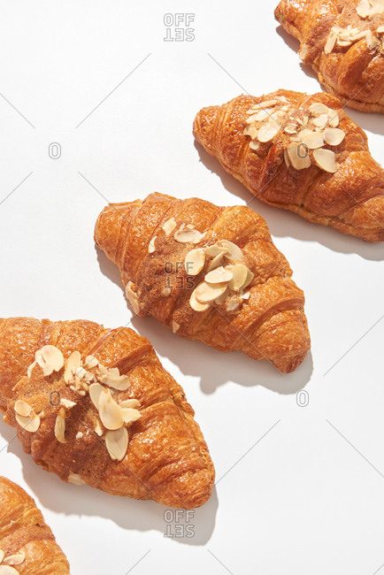 Close up view freshly baked french homemade croissants with almond crumbs on a light grey background with hard shadows, copy space. Top view. Concept of breakfast continental.