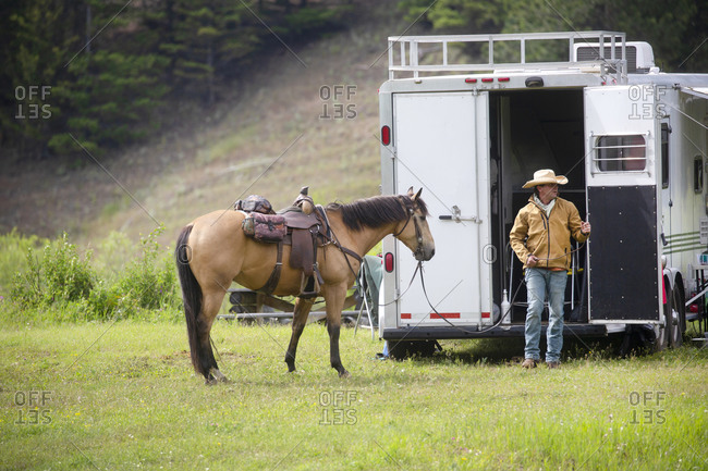 Rancher standing beside a trailer with his horse