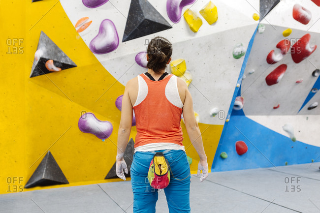 Adult woman standing in front of a rock climbing wall wearing an orange tank top and blue pants