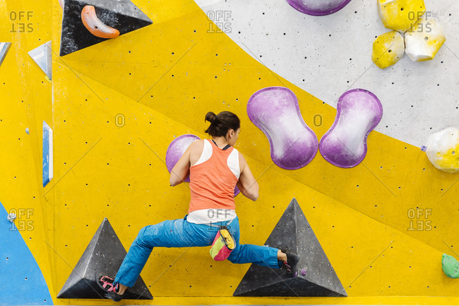 Adult woman wearing an orange tank top and blue pants rock climbing indoors