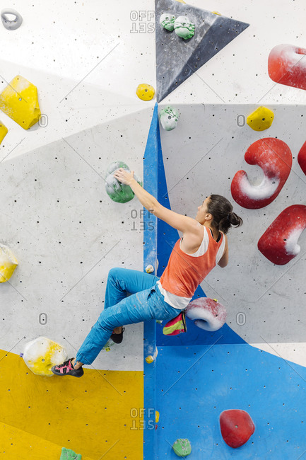 Woman wearing an orange tank top and blue pants rock climbing indoors