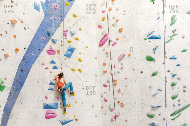 Woman wearing an orange tank top and blue pants climbing on indoor rock wall