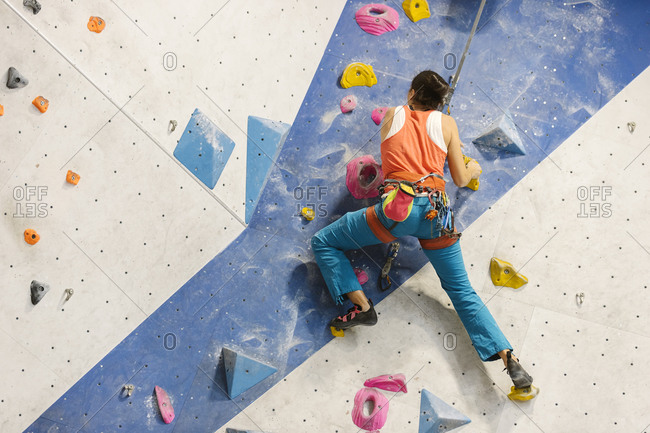Adult woman wearing an orange tank top and blue pants climbing on indoor rock wall