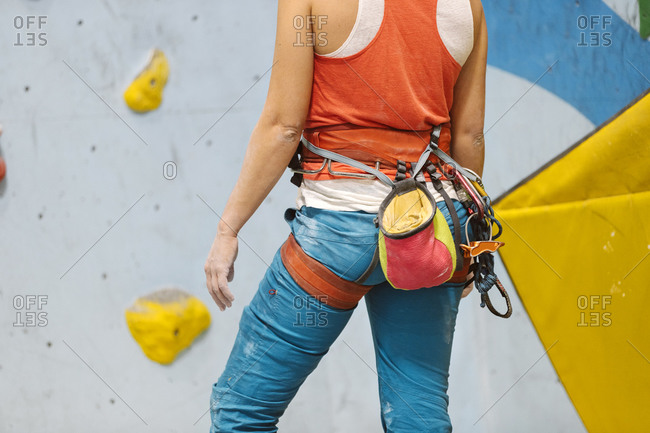 Adult woman standing in front of a rock climbing wall