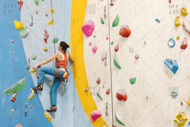Woman climbing up colorful indoor rock wall