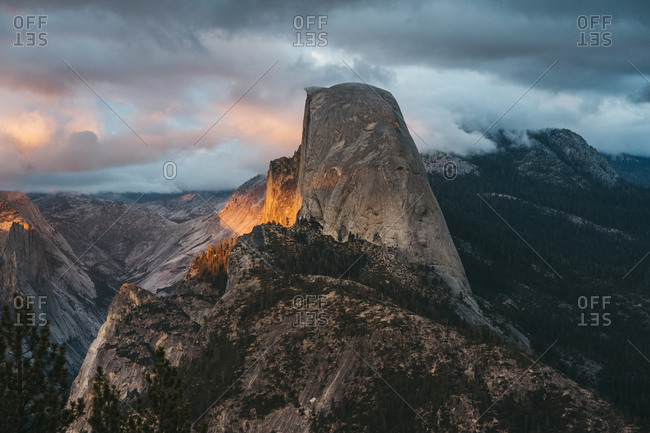 Glowing sunset illuminates the clouds and Half Dome of Yosemite