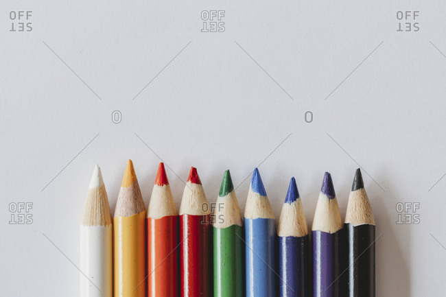 Rainbow of coloring pencils on plain white background
