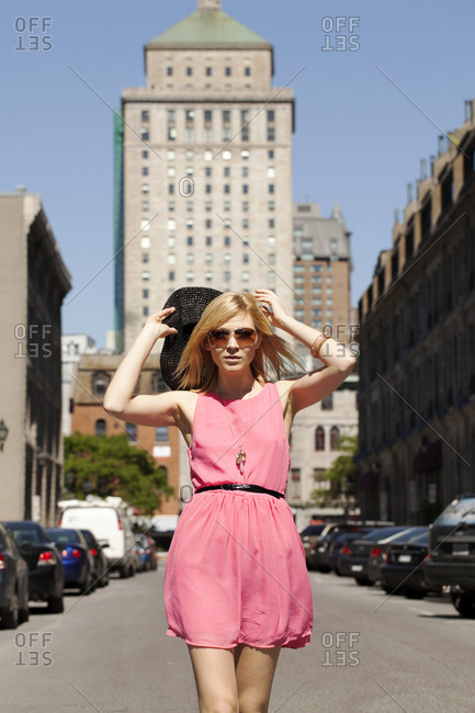 Woman in pink dress walking in city