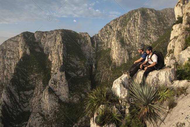 Monterrey, Mexico - October 7, 2018: Two friends sitting on a rock in a high point at La Huasteca