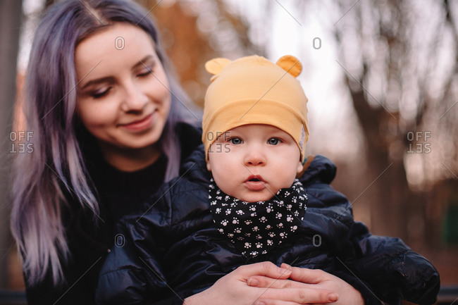 Happy young mother holding baby son while sitting on bench in park