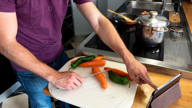 Online cooking lessons through a tablet, preparing to cut vegetables