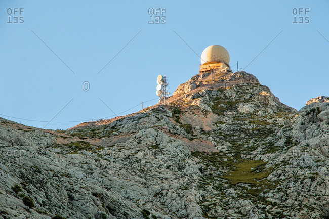 Radar dome station and radio antennas on top of a mountain at sunset