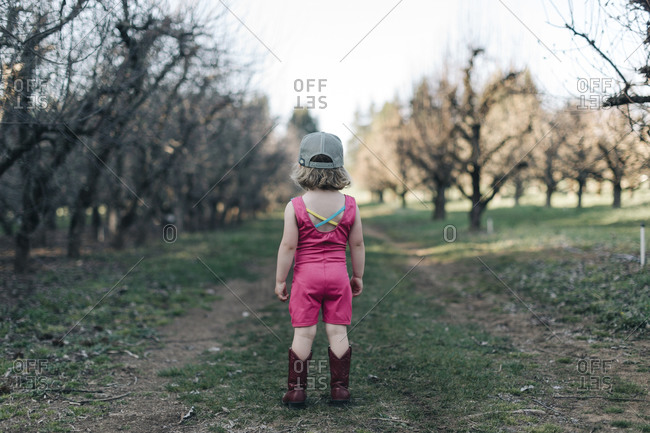 A young girl stands in an orchard wearing a leotard and cowgirl boots.