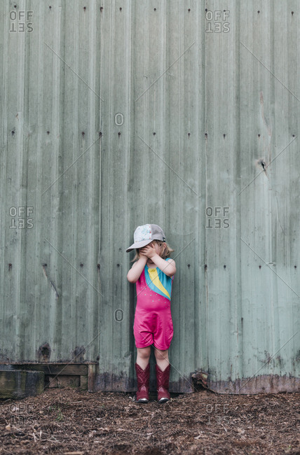 A young girl stands near a barn wearing a leotard and cowgirl boots.