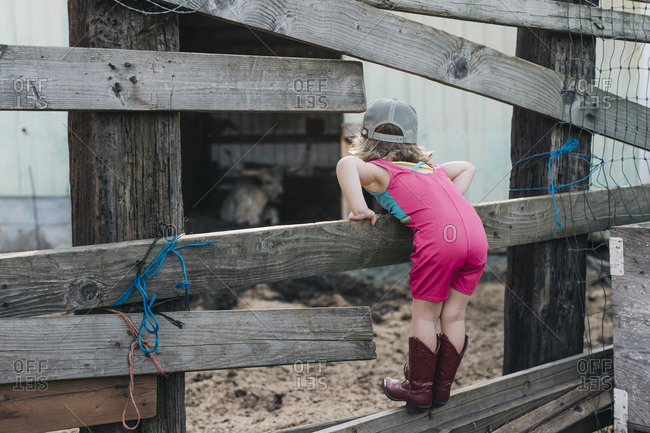A young girl stands on a fence wearing a leotard and cowgirl boots.