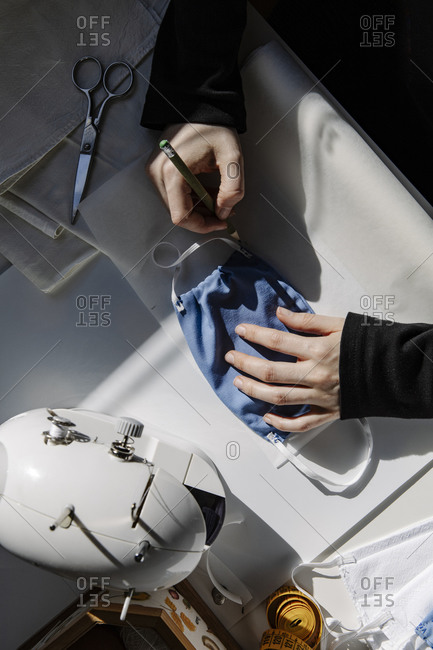 Top view of craftswoman taking measures of mask in workshop