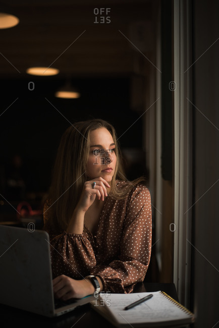 Young blogger influencer working in coffee shop by a window