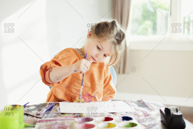 Young girl sitting and painting inside