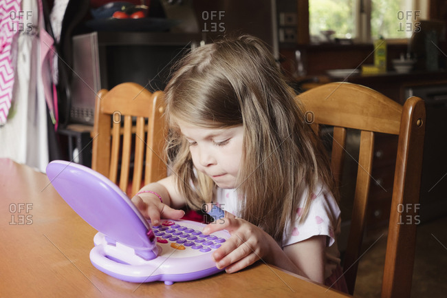 Young girl playing on preschool tablet