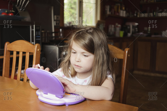 Young girl sitting and playing on preschool tablet