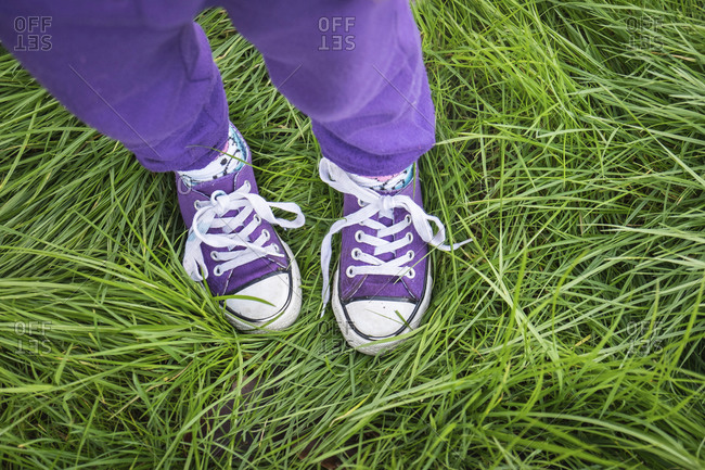 Girl wearing purple pants and shoes standing in long green grass