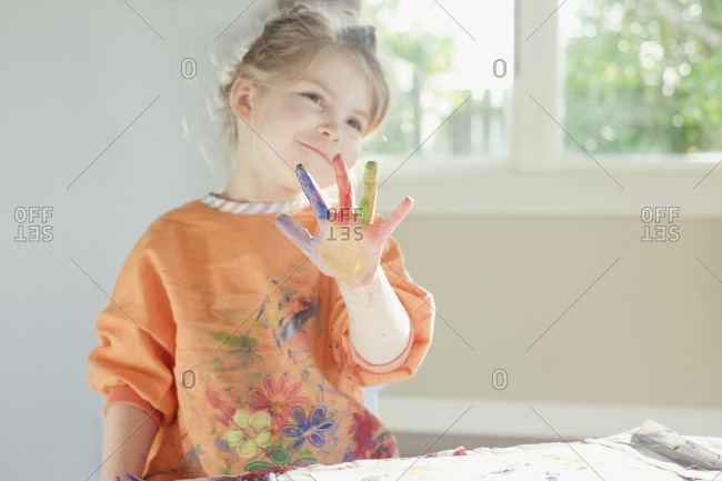 Young girl smiling with paint on her hand