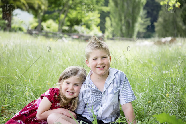 Young boy and girl sitting in green grass looking at the camera
