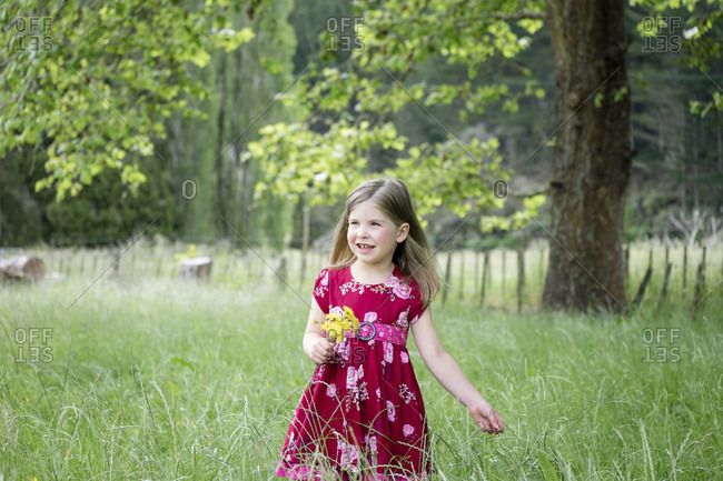 Young girl walking through long green grass holding yellow flowers