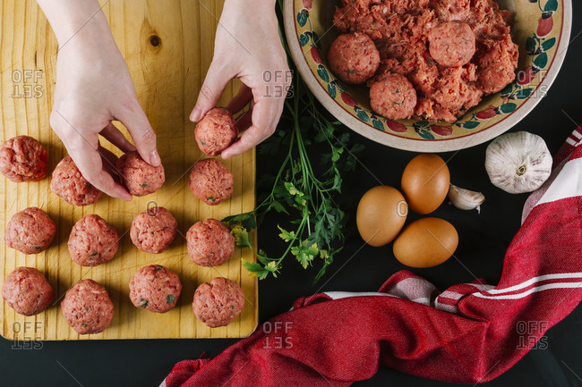 Woman makes homemade meatballs with minced meat seasoned with spices