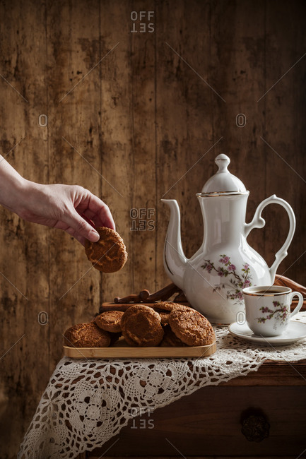 Hand taking homemade cookies with coffee in vintage dishware