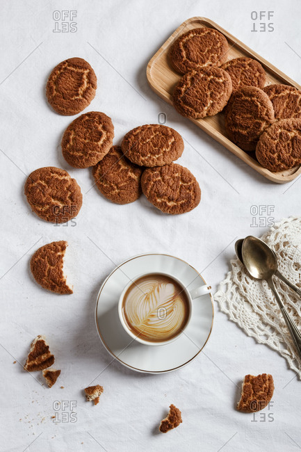 Delicious coffee with a drawing made with cream and homemade cookies