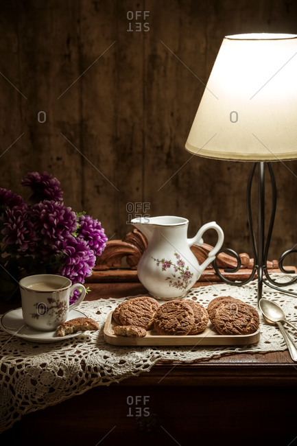 Homemade cookies with coffee on rustic table illuminated with a lamp