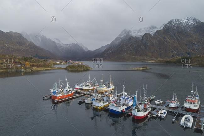Tromso, Troms og Finnmark, Norway - October 7, 2019: Boats docked in port in Lofoten fjords from drone view