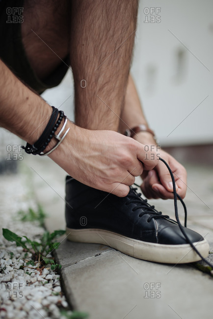 Urban young guy tying his shoe, getting ready to go