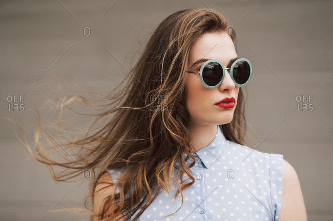portrait of a woman with green sunglasses on a windy day