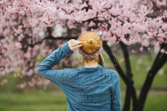 Back view of redhead woman standing in front of cherry blossom tree