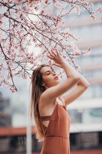 Fashion portrait of young woman in jumpsuit under the  blossom tree