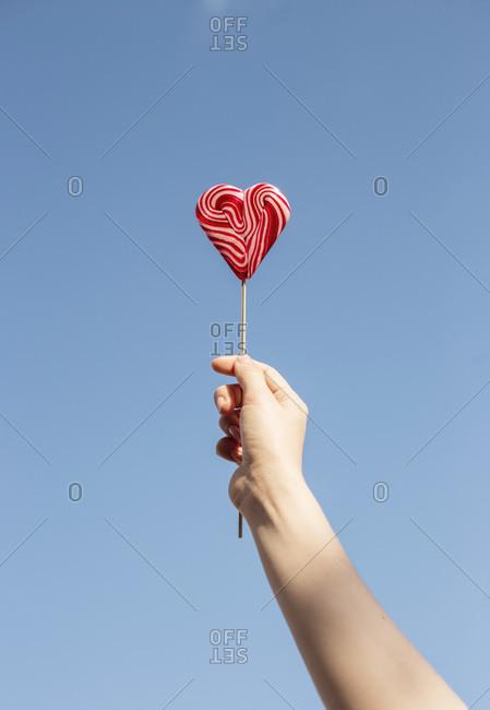 Woman's hand holding heart shaped lollipop