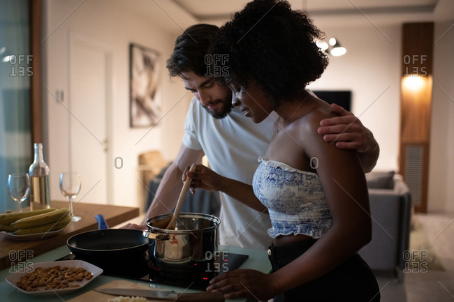Multiethnic couple cooking romantic dinner together