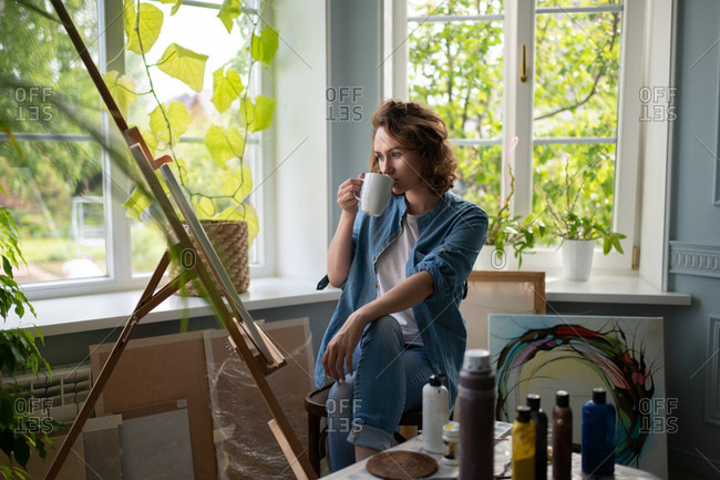 Woman admiring artwork in home studio