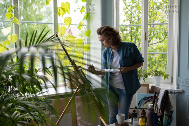 Woman painting near window in home studio