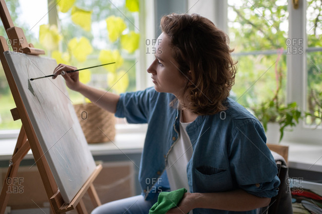 Concentrating female painting on easel
