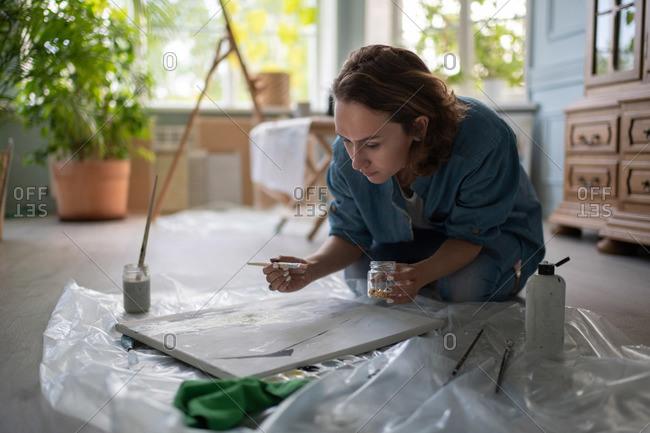 Adult woman painting on floor