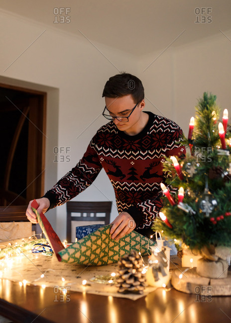 Young man packs Christmas presents for friends and family