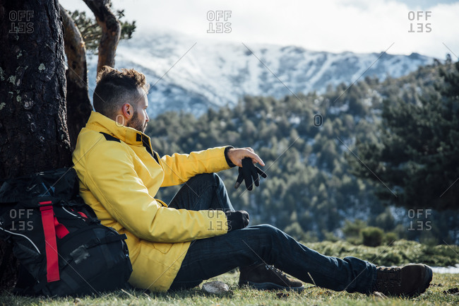 Young man with yellow jacket and backpack sitting on the mountain.