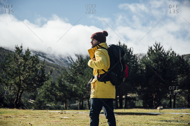 Young man with yellow jacket and backpack in the mountains.
