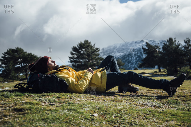 Young man with yellow jacket and backpack lying on the mountain.