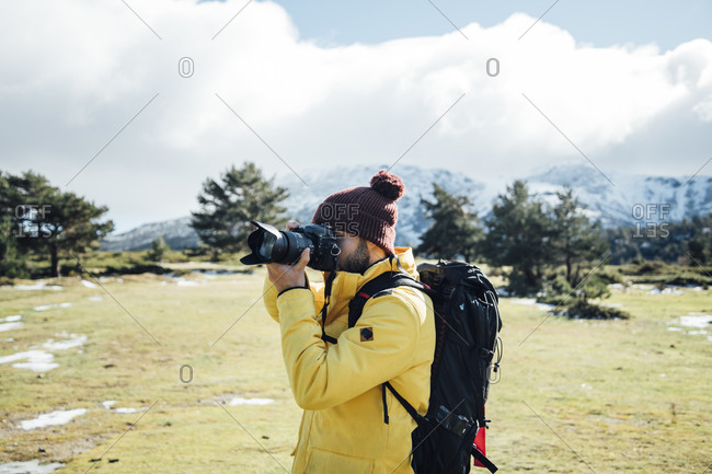 Young man with yellow jacket and backpack taking pictures on the mount