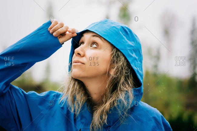Woman standing in the rain with a raincoat on looking up at the sky