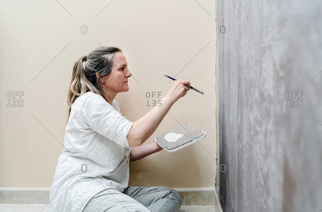 Blonde barefoot woman sitting on her floor starts painting a wall gray